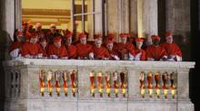 Cardinals watch as Pope Francis speaks to the crowd from the central balcony of St. Peter's Basilica at the Vatican, Wednesday, March 13, 2013. (Andrew Medichini/AP)