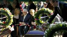 Peter Abraham, right, places at rose on the casket of his uncle, Flight Lieutenant Peter Campbell, at the funeral for him and Leading Aircraftsman Theodore Bates at Woodlawn Memorial Park in Guelph, Ont., on Sept. 17, 2013. The two airmen were lost over Lake Muskoka in 1940. (Peter Power/The Globe and Mail)