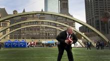 Mayor Rob Ford prepares to make a play during a short game of touch football as part of the 100th Grey Cup celebrations in Toronto. (Peter Power/The Globe and Mail)