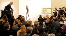Auctioneer Henry Wyndam sells the sculpture 'Walking Man I' or 'L'Homme qui marche I', by Alberto Giacometti, at Sotheby's auction rooms in London, Wednesday Feb. 3, 2010. The life-size bronze sculpture of a man by Alberto Giacometti was sold at the London auction for 65 million pounds (US$104 million). Sotheby's says the sale set a world record for the most expensive work of art ever sold at auction. The auction house said Wednesday it took just eight minutes for bidders to reach the hammer price for the item. (AP Photo / Anthony Devlin, pa) **UNITED KINGDOM OUT: NO SALES: NO ARCHIVE:** (ANTHONY DEVLIN/Press Association)