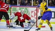 Switzerland's goalie Melvin Nyffeler tries to save a shot from Sweden's Oskar Sundqvist, right, during the first period of their qualification round IIHF World Junior Hockey Championships action in Malmo, Sweden, on Thursday Dec. 26, 2013. (LUDVIG THUNMAN/AP)