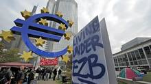 Demonstrators stand between protest banners underneath the euro sign in front of the European Central Bank in Frankfurt, central Germany, Monday, Oct. 17, 2011. Protestors gathered at many major European cities last Saturday to join in demonstrations against corporate greed and inequality and to support the US movement ' Occupy Wall Street'. About 150 protestors in Frankfurt remained at that place , some with tents. (Thomas Lohnes/Thomas Lohnes/Associated Press)