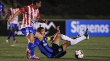 Davy Arnaud (R) of Canada's Montreal Impact falls as he fights for the ball against Robert Arias of Guatemala's CD Heredia during their CONCACAF Champions League soccer match at Cementos Progreso Stadium in Guatemala City, August 21, 2013. (JORGE DAN LOPEZ/REUTERS)