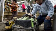 Kids play in a sandbox at a daycare centre while Premier Christy Clark speaks during a news conference in Vancouver in 2011. (John Lehmann/The Globe and Mail)
