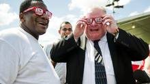 Toronto Mayor Rob Ford, right, and Toronto Councillor Michael Thompson, left, try on sunglasses from HEB, a local grocery store, during a tour of the Austin City Limits music festival at Zilker Park in Austin, Texas on Fri., Oct. 3, 2013. (Ashley Landis/Ashley Landis)