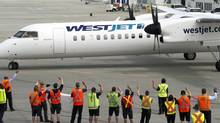 Ground crew wave at WestJet Encore's first flight, this one going from Calgary to Nanaimo. Encore is flying new Bombardier Q400 regional airplanes to service smaller destinations. (Larry MacDougal For The Globe and Mail)