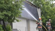 Firefighters continue to douse small fires in the roof of a townhouse complex in Brampton, Ont., on June 8, 2014. (J.P. MOCZULSKI FOR THE GLOBE AND MAIL)