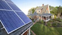 Outfitting a house with solar energy panels is one step towards creating a net-zero energy building. (Stephan Savoia/Associated Press)