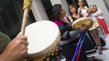 Members of the Secwepemc Women Warrior Society sing and beat drums while protesting against Imperial Metals outside of the Toronto Stock Exchange on August 7, 2014. (Darren Calabrese/The Canadian Press)