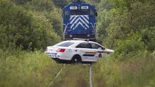 RCMP officers guard one of five locomotives about a kilometre away from the crash site July 9, 2013 in Lac-Mégantic, Quebec. Police have confirmed that the rail cars are being treated as a crime scene. (Moe Doiron/The Globe and Mail)