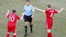 England's Wayne Rooney and teammate Steven Gerrard complain to referee Jorge Larrionda of Uruguay. (KIM KYUNG-HOON/Reuters)