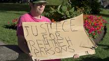 Protester Donald Smith, from Calgary, stands outside provincial court in Halifax on Aug. 15, 2013. Two Halifax men facing child pornography charges after the death of Rehtaeh Parsons appeared in court and the case was put over until Sept. 19 while the defence seeks additional disclosure of evidence. (Andrew Vaughan/THE CANADIAN PRESS)
