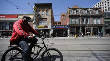 A cyclist on Queen Street West in Toronto. City staff are recommending enhancements to downtown cycling infrastructure, potentially setting up a conflict with motorists and pro-car councillors. (Fred Lum/The Globe and Mail)