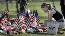 A mourner visits the makeshift memorial on the campus of Virginia Tech in Blacksburg, Va., Monday, April 23, 2007. A moment of silence was held for the students and faculty killed by gunman Seung-Hui Cho. (Evan Vucci/AP)