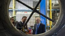 Quebec Liberal Leader Jean Charest, right, alongside Techniflamme Combustion owner and president Frederic Millard, left, takes a look at an asphalt drum during a tour of the engineering plant while on an election campaign stop in Richmond, Que., Tuesday, August 7, 2012. (Graham Hughes/Canadian Press)
