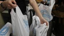 Customers receive plastic biodegradable plastic bags when shopping at Noah's Natural Foods on Yonge St., Toronto on November 26, 2008. Toronto's public works committee voted in favour of abandoning the issue once and for all on June 19, 2013. (Fernando Morales/The Globe and Mail)