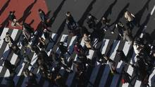 Pedestrians cross a Tokyo street in this photo from Dec. 13. 2012. Japan is running a budget deficit of about 10 per cent of gross domestic product and its gross debt has risen from less than 68 per cent of GDP in 1990 to more than 235 per cent now. (YURIKO NAKAO/REUTERS)