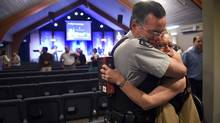 RCMP Constable Jim Shields receives a hug from Elisabeth French after a church service at the Hillside Baptist Church on June 8. (Fred Lum/The Globe and Mail)