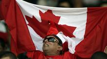 A supporter holds up a Canadian flag before a World Cup 2014 qualifying soccer game between Canada and Cuba. (Associated Press)
