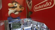 Shoppers walk under the logo of Nintendo and Super Mario characters at an electronics store in Tokyo Wednesday, May 7, 2014. (Shizuo Kambayashi/AP)
