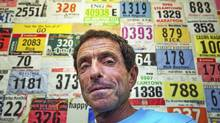 Rick Rayman stands in front of a wall of his running bibs and jackets he's recevied from some of the 231 marathons he's run since he began running in 1978. (Della Rollins for the Globe and Mail./Della Rollins for the Globe and Mail.)