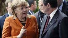 German Chancellor Angela Merkel is greeted by Cyprus' presidential race's forerunner and president of the right-wing Democratic Rally party Nicos Anastasiades upon her arrival at a European People's Party (EPP) summit in the Cypriot town of Limassol Jan. 11, 2013. (JAMAL SAIDI/REUTERS)