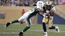 Winnipeg Blue Bombers' Nic Grigsby (R) is tackled by Saskatchewan Roughriders' Rod Williams during the first half of their CFL football game in Winnipeg August 7, 2014. (FRED GREENSLADE/REUTERS)