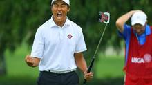 Gunn Yang, of San Diego, Calif., and his caddy Richard Grice react to sinking his par putt on the 17th hole during the afternoon round to win the 36-hole championship match of the 2014 U.S. Amateur Championship at Atlanta Athletic Club on Sunday, Aug.17, 2014, in Johns Creek, Ga. (Curtis Compton/AP)