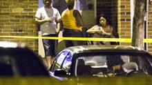 People sit at a crime scene following a shooting in Scarborough, a suburb in east Toronto, July 17, 2012. (MARK BLINCH/REUTERS)