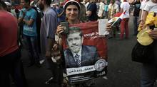 A female supporter of presidential candidate, Mohammed Morsi, carries a poster with his picture during celebrations claiming victory over rival candidate, Ahmed Shafiq, in Tahrir Square, Cairo, Egypt, Monday, June 18, 2012. (Nasser Nasser/AP)