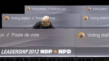 A worker constructs voting stations as the NDP get ready for the party leadership convention in Toronto on Wednesday, March 21, 2012. (Nathan Denette/THE CANADIAN PRESS/Nathan Denette/THE CANADIAN PRESS)