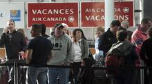 Passengers wait to rebook their flights after Air Canada baggage handlers walked off the job at Pierre Trudeau airport in Montreal, March 23, 2012. (Ryan Remiorz/The Canadian Press/Ryan Remiorz/The Canadian Press)