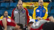 Team Northwest Territories/Yukon skip Jamie Koe (L) and his brother, Team Alberta skip Kevin Koe (R), guide their teams during the fourth end at the 2014 Tim Hortons Brier curling championships in Kamloops, British Columbia March 3, 2014. (BEN NELMS/REUTERS)