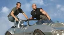 "Paul Walker, left, and Vin Diesel in a scene from ""Fast Five,"" a movie that is already a hit overseas. (Jaimie Trueblood/AP)"