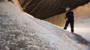 Trevor Berg holds some potash chiclets in a storage build at the Potash Cory mine near Saskatoon