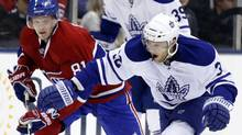Toronto Maple Leafs forward Kris Versteeg goes after a loose puck against Montreal Canadiens forward Lars Eller (L) during the first period of their NHL hockey game in Toronto December 11, 2010. The Leafs won 3-1. REUTERS/Mike Cassese (MIKE CASSESE)
