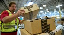 An employee stacks boxes filled with merchandise for shipment at the Amazon.com Inc. distribution center in Phoenix, Arizona, on Nov. 26, 2012. (David Paul Morris/Bloomberg)