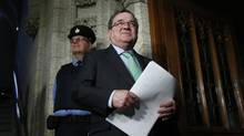 Canada's Finance Minister Jim Flaherty speaks to journalists while walking to the House of Commons on Parliament Hill in Ottawa on Dec. 9, 2013 (CHRIS WATTIE/REUTERS)