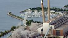 The third of four smokestacks, known as the Four Sisters, at a the defunct coal-fired plant in Mississauga crumbles during a controlled demolition June 12, 2006. (Mike Cassese/Reuters)