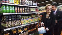 Ontario Premier Kathleen Wynne, left, and Minister of Finance Charles Sousa choose beer at a Loblaws grocery store in Toronto on Dec. 15. (Nathan Denette/THE CANADIAN PRESS)