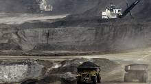 Mining trucks operate at the Albian Sands oils sands project near Fort McMurray, Alta. (JEFF MCINTOSH/AP)