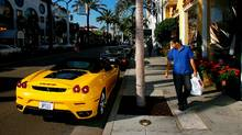 A man glances at a Ferrari sports car while visiting businesses that cater to high-end luxury item consumers along Rodeo Drive. (David McNew/Getty Images)
