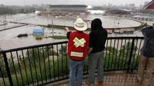 Calgarians look out over a flooded Calgary Stampede grounds and Saddledome in Calgary, Friday, June 21, 2013. (Jeff McIntosh/THE CANADIAN PRESS)
