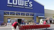 Lowe's workers collect shopping carts in the parking lot at the Lowe's Home Improvement Warehouse in Burbank, Calif. (FRED PROUSER/REUTERS)