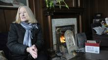 Diana Swift, whose Toronto home has been without power since last Sunday, rubs her constantly cold hands while sitting beside her fireplace on Dec. 29, 2013. (J.P. MOCZULSKI FOR THE GLOBE AND MAIL)