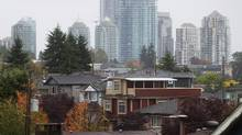 Condos in the Gilmore area of Burnaby are seen in the distance behind houses in east Vancouver, B.C., on Sunday September 20, 2015. (DARRYL DYCK/The Globe and Mail)