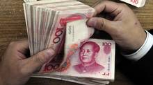 An employee counts Renminbi banknotes at a Bank of China branch in Hefei, Anhui province. (STRINGER SHANGHAI/REUTERS)