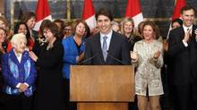 Prime Minister Justin Trudeau takes part in celebrating International Women's Day with his wife Sophie Gregoire-Trudeau and Finance Minister Bill Morneau (far right) along with women from his caucus in Ottawa on Tuesday. (FRED CHARTRAND/THE CANADIAN PRESS)