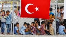 Refugees wait for the arrival of officials at Nizip refugee camp near Gaziantep, Turkey, on April 23, 2016. (UMIT BEKTAS/REUTERS)