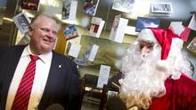 Mayor Rob Ford Ford, left, receives candy canes from a man dressed as Santa Claus, outside of Ford's office at City Hall in Toronto.(Peter Power/The Globe and Mail) (Peter Power/The Globe and Mail)